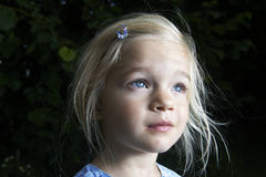 Portrait of child blond girl looking up stock photography