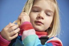 Portrait of child blond girl. Stroking her hair. Blue sky background Stock Photo