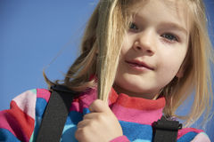 Portrait of child blond girl. Stroking her hair. Blue sky background Royalty Free Stock Image