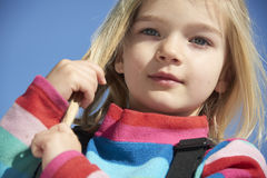 Portrait of child blond girl. Stroking her hair. Blue sky background Stock Photography