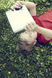 Portrait of Child blond young boy playing with a digital tablet computer outdoors  lying on grass. Playing game or listening music or watching movie Royalty Free Stock Photography