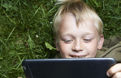 Portrait of Child blond young boy playing with a digital tablet. Computer outdoors  lying on grass, listening music or watching movie, facial expression Stock Photo
