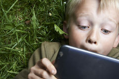 Portrait of Child blond young boy playing with a digital tablet. Computer outdoors  lying on grass, listening music or watching movie Stock Photos
