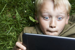 Portrait of Child blond young boy playing with a digital tablet. Computer outdoors  lying on grass, listening music or watching movie, facial expression Royalty Free Stock Photo