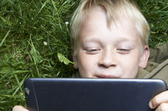 Portrait of Child blond young boy playing with a digital tablet. Computer outdoors  lying on grass, listening music or watching movie, facial expression Royalty Free Stock Image