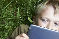 Portrait of Child blond young boy playing with a digital tablet. Computer outdoors  lying on grass, listening music or watching movie, facial expression Stock Photos
