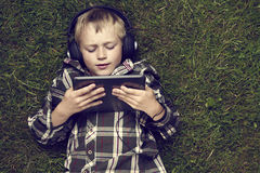 Portrait of Child blond young boy playing with a digital tablet computer outdoors lying on grass. Listening music or watching movie with headphones stock image