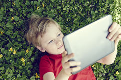 Portrait of Child blond young boy playing with a digital tablet Royalty Free Stock Images