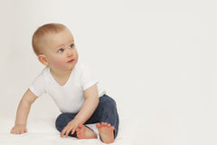 Portrait of a child with blue eyes on a gray background In jeans and a white T-shirt stock photos