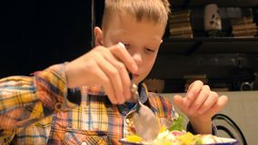Child boy is eating dessert with ice cream cookies and fruits in a white plate. Portrait of child boy is eating sweet tasty dessert with ice cream, cookies stock video