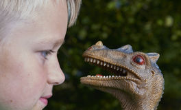 Portrait of child boy playing with toy dinosaur Stock Photo