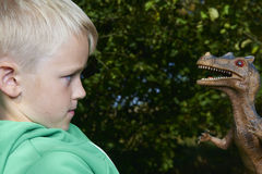 Portrait of child boy playing with toy dinosaur Stock Image