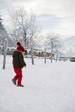 Portrait of child in brown jacket and red knitted hat and red tr. Ousers, lots of snow. Winter forest Royalty Free Stock Image