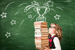 Portrait of child in classroom. Against chalkboard. Kid with books in class. Success, idea and win concept. Back to school stock images