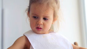 Portrait of a child closeup that eats the food. The child emotionally eat breakfast. Caucasian little girl independently eats. Small child eats appetizing stock footage