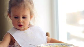 Portrait of a child closeup that eats the food. The child emotionally eat breakfast. Caucasian little girl independently eats. Small child eats appetizing stock video