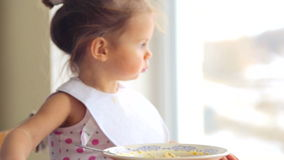 Portrait of a child closeup that eats the food. The child emotionally eat breakfast. Caucasian little girl independently eats. Small child eats appetizing stock video footage
