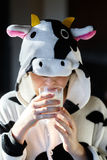 Portrait of child with cow pajamas, holding a glass of milk Royalty Free Stock Images