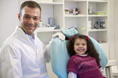 Portrait of child and dentist in dental studio, looking at camer Royalty Free Stock Images