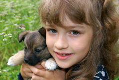 Portrait of the child with a dog. The happy girl holds a small puppy on hands Stock Photo