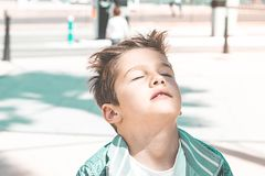 Portrait of a child with eyes closed and hair in the wind. Expression of peace and freedom for a child royalty free stock photo