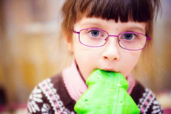Portrait of child girl biting gingerbread Royalty Free Stock Photography