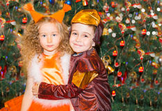 Portrait of child girl and boy in a suit squirrels around a Christmas tree decorated. Kids on holiday new year Royalty Free Stock Images