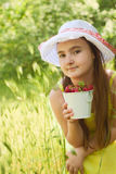 Portrait of child girl with bucket of strawberries Royalty Free Stock Image