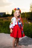 Portrait of a child girl in ethnic ukrainian costume on a meadow in summer. stock photos