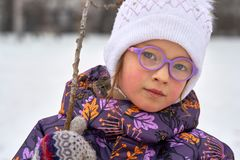 Portrait of a child girl in glasses on a winter walk.   The girl is dressed in a hat and jacket.   A cloudy winter day. Royalty Free Stock Photos