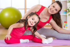 Portrait of child girl and mother doing physical exercise at home stock photography