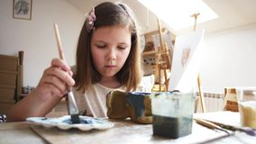 Child girl is painting in blue her handmade toy from clay in art workshop. Portrait of child girl paints in blue her handmade toy from clay, she dips the brush stock video footage