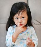Portrait of child girl with snot flowing from her nose.  Royalty Free Stock Image
