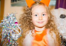 Portrait of child girl in a suit squirrels around a Christmas tree decorated. Kid on holiday new year Royalty Free Stock Image