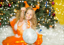 Portrait of child girl in a suit squirrels around a Christmas tree decorated. Kid on holiday new year Stock Photo