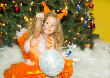 Portrait of child girl in a suit squirrels around a Christmas tree decorated. Kid on holiday new year Stock Images