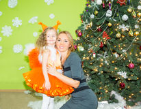 Portrait of child girl in a suit squirrels with mother around a Christmas tree decorated. Kid on holiday new year Stock Photo