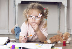 Portrait of a child in glasses with markers. The girl lies on the floor and draws markers Royalty Free Stock Photos