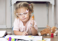 Portrait of a child in glasses with markers. The girl lies on the floor and draws markers Stock Images