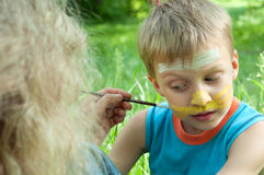 Portrait of a child with his face being painted Royalty Free Stock Image