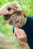 Portrait of a child with his face being painted Stock Photos