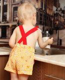 Portrait of a child holding  cup at the kitchen. Portrait of a child holding a cup at the kitchen at home Royalty Free Stock Photos