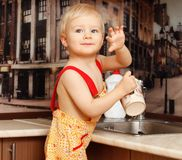 Portrait of a child holding  cup at the kitchen. Portrait of a child holding a cup at the kitchen at home Stock Photos