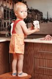 Portrait of a child holding a cup at the kitchen. At home Stock Photo