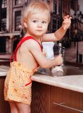 Portrait of a child holding  cup at the kitchen. Portrait of a child holding a cup at the kitchen at home Royalty Free Stock Image