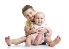 Portrait of child hugging his little cute sister sitting on floor isolated on white background royalty free stock photo