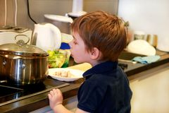 Portrait of child in kitchen. Cute little boy, playing in kitchen. Young kid is hungry, looks at and checks is it finished lunch. stock photos