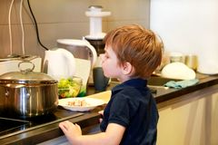 Portrait of child in kitchen. Cute little boy, playing in kitchen. Young kid is hungry, looks at and checks is it finished lunch. stock photography