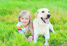 Portrait child and labrador retriever dog lying on grass Royalty Free Stock Photography