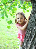 Portrait of child little girl near tree in summer Royalty Free Stock Photo